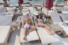 Pares jovenes que se relajan en un balneario Foto de archivo