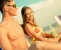 Pares jovenes que se relajan en una playa Foto de archivo