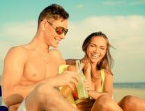Pares jovenes que se relajan en una playa Foto de archivo libre de regalías