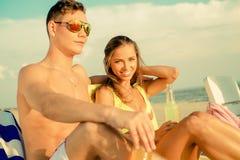 Pares jovenes que se relajan en una playa Fotografía de archivo libre de regalías