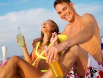 Pares jovenes que se relajan en una playa Imágenes de archivo libres de regalías
