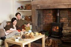 Pares jovenes que se relajan por el fuego Imagen de archivo libre de regalías