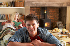 Pares jovenes que se relajan por el fuego Foto de archivo libre de regalías