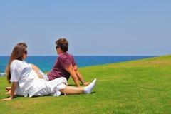 Pares jovenes que se relajan por el mar Foto de archivo