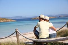 Pares jovenes que se relajan por el mar Imagenes de archivo