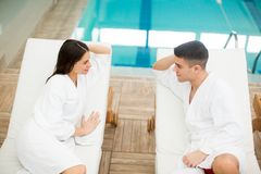 Pares jovenes que se relajan por la piscina Imágenes de archivo libres de regalías