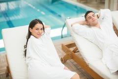 Pares jovenes que se relajan por la piscina Foto de archivo libre de regalías
