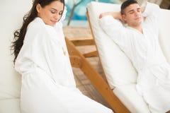 Pares jovenes que se relajan por la piscina Imagen de archivo
