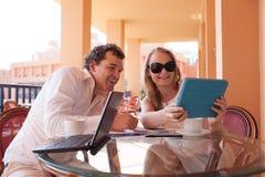 Pares jovenes que se relajan sobre el café en un balcón Imágenes de archivo libres de regalías
