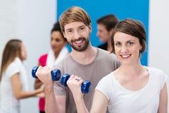 Pares jovenes que se resuelven en el gimnasio Imagen de archivo libre de regalías