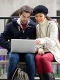Pares jovenes que se sientan al aire libre mirando el ordenador portátil junto Imágenes de archivo libres de regalías
