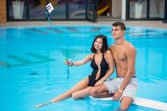 Pares jovenes que se sientan al borde de la piscina y que toman la foto del selfie en el teléfono con el palillo del selfie Fotografía de archivo libre de regalías