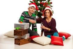 Pares jovenes que se sientan cerca de árbol de Navidad Imágenes de archivo libres de regalías