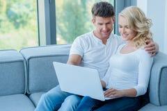 Pares jovenes que se sientan compartiendo un ordenador portátil Imagen de archivo