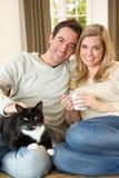 Pares jovenes que se sientan con el gato en el sofá Foto de archivo