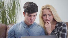 Pares jovenes que se sientan delante del ordenador portátil en casa Retrato de un hombre moreno y de una mujer rubia que comprueb metrajes