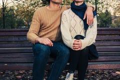 Pares jovenes que se sientan en banco de parque Fotos de archivo libres de regalías