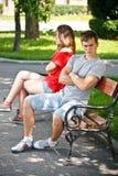 Pares jovenes que se sientan en banco en parque Fotos de archivo