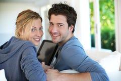Pares jovenes que se sientan en casa con la tableta Fotografía de archivo