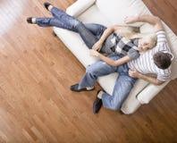 Pares jovenes que se sientan en el asiento de amor Imagen de archivo libre de regalías