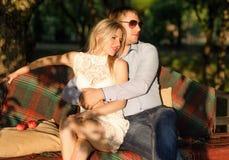 Pares jovenes que se sientan en el banco del jardín Imagen de archivo libre de regalías