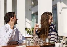 Pares jovenes que se sientan en el café al aire libre que pide la cuenta foto de archivo libre de regalías