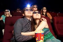 Pares jovenes que se sientan en el cine, mirando una película Fotografía de archivo