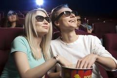 Pares jovenes que se sientan en el cine, mirando una película Imagen de archivo