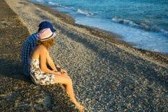 Pares jovenes que se sientan en el mar en la puesta del sol Fotografía de archivo libre de regalías