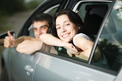 Pares jovenes que se sientan en el nuevo coche Fotos de archivo