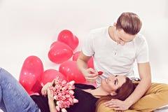 Pares jovenes que se sientan en el piso con los globos en la forma de Foto de archivo libre de regalías