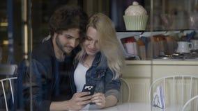 Pares jovenes que se sientan en el restaurante que mira en la pantalla del smartphone y que juega al juego en medios sociales almacen de video