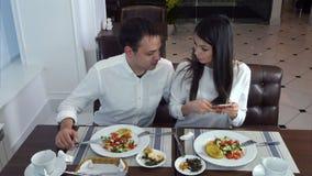 Pares jovenes que se sientan en el restaurante y que toman las imágenes de la comida con el teléfono móvil almacen de metraje de vídeo