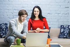 Pares jovenes que se sientan en el sofá, el coffe de consumición o el té y usando un ordenador portátil Imagen de archivo