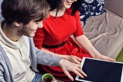 Pares jovenes que se sientan en el sofá, el coffe de consumición o el té y usando un ordenador portátil Opinión del primer Imágenes de archivo libres de regalías