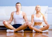 Pares jovenes que se sientan en el suelo Meditating imagenes de archivo