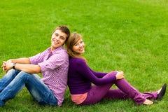 Pares jovenes que se sientan en hierba Imágenes de archivo libres de regalías