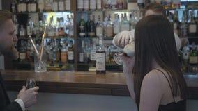 Pares jovenes que se sientan en la barra en un restaurante costoso o un pub El hombre confiado barbudo bebe el whisky y su almacen de metraje de vídeo