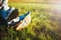 Pares jovenes que se sientan en la hierba en el sol fotografía de archivo