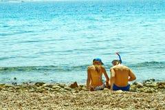 Pares jovenes que se sientan en la orilla del Mar Rojo foto de archivo