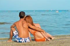 Pares jovenes que se sientan en la playa arenosa y el abarcamiento Fotos de archivo libres de regalías