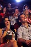 Pares jovenes que se sientan en la sonrisa del cine Imagen de archivo libre de regalías