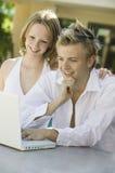 Pares jovenes que se sientan en la tabla del patio trasero usando el ordenador portátil Fotos de archivo libres de regalías