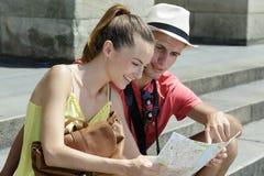 Pares jovenes que se sientan en los pasos que sonríen mirando el mapa foto de archivo libre de regalías