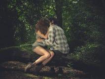 Pares jovenes que se sientan en registro y besarse Imágenes de archivo libres de regalías