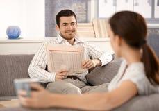 Pares jovenes que se sientan en sala de estar en el sofá foto de archivo libre de regalías