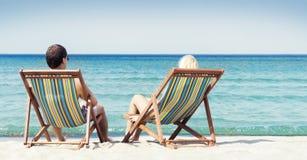 Pares jovenes que se sientan en sillas de playa Imágenes de archivo libres de regalías