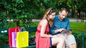 Pares jovenes que se sientan en un banco con los panieres y la tableta coloridos. Imagen de archivo