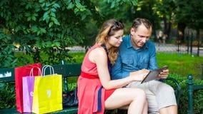 Pares jovenes que se sientan en un banco con los panieres y la tableta coloridos. Foto de archivo libre de regalías