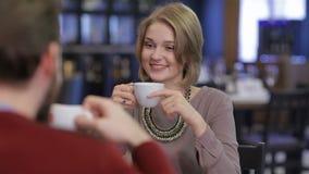 Pares jovenes que se sientan en un café de consumición del café y almacen de video